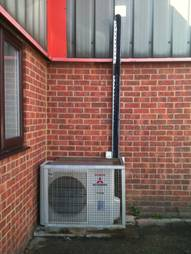 server room outdoor air conditioning unit installed outside of building with basic cage system